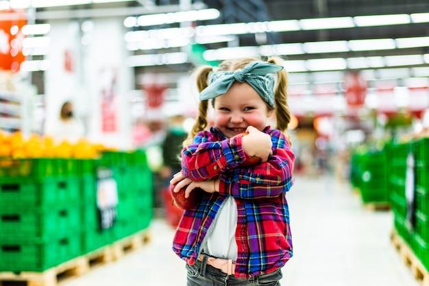 Petite fille choisissant une pomme dans un magasin d'alimentation ou un supermarché