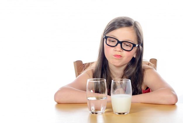 Une petite fille a le choix entre eau et lait