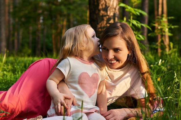 Une petite fille chuchote quelque chose à l'oreille de sa mère lors d'un pique-nique dans une forêt ou un parc