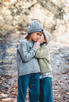 Petite fille chuchote un secret à ses sœurs assis sur fond de nature. amitié soeurs