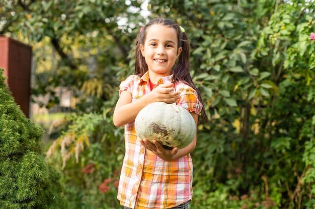 Petite fille avec une citrouille dans le jardin