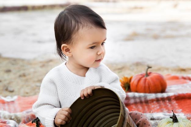 Petite fille avec des citrouilles tenant un seau en plein air
