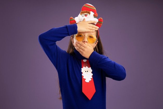 Petite fille en col roulé bleu avec cravate rouge et drôle de jante de noël sur la tête inquiète avec la main sur son front et c