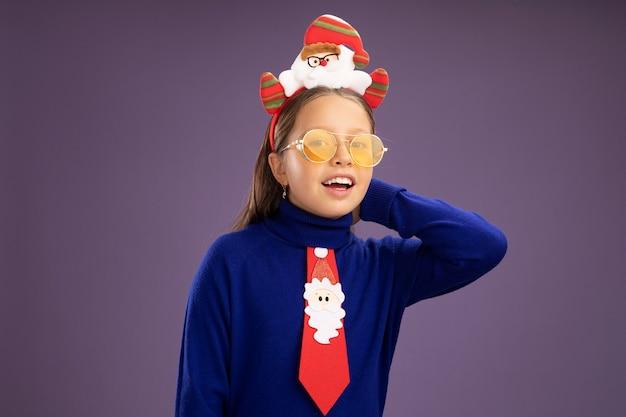 Petite fille en col roulé bleu avec cravate rouge et jante de noël drôle sur la tête regardant la caméra avec un visage heureux souriant joyeusement debout sur fond violet