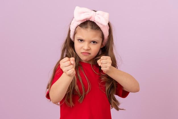 Petite fille en colère sur fond rose montre son poing.
