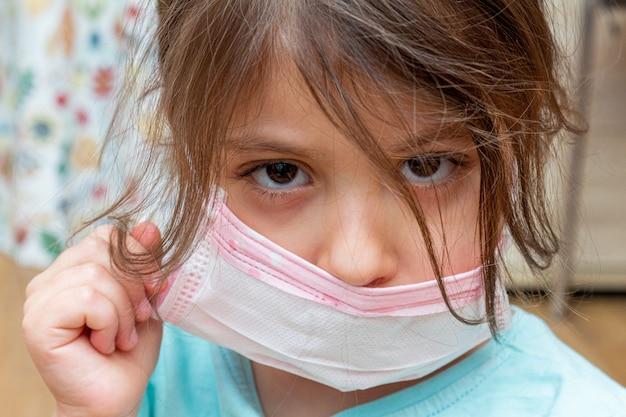 Petite fille en colère portant un masque de protection médical à la maison pendant l'isolement en quarantaine