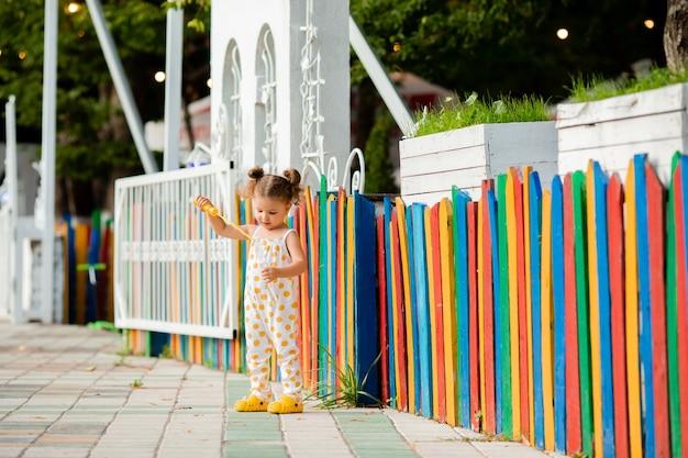 Une petite fille en combinaison joue avec des bulles de savon dans le contexte d'une clôture multicolore