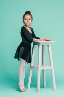 La petite fille comme danseuse balerina près de chaise sur studio bleu