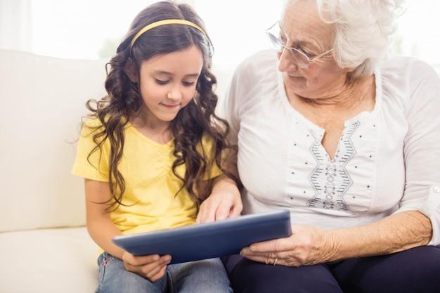 Petite-fille concentrée à l'aide d'une tablette avec sa grand-mère à la maison