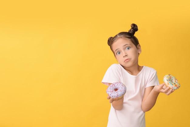 Petite fille confuse avec des beignets sucrés