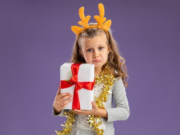 Petite fille confuse portant cerceau de cheveux de noël avec guirlande sur le cou tenant la boîte-cadeau isolé sur fond bleu
