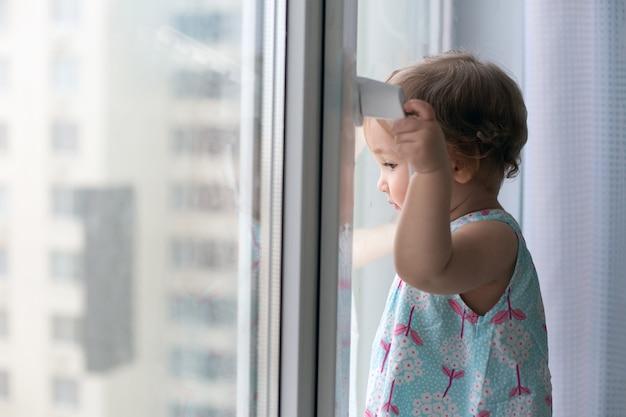Petite fille contre la fenêtre fermée donnant sur.