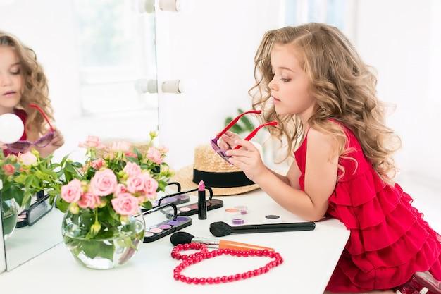 Une petite fille avec des cosmétiques assis près du miroir.