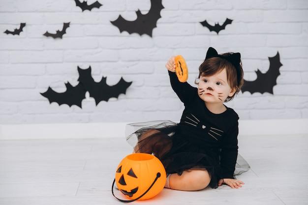 Une petite fille en costume de chat noir avec un panier de citrouille tenant un pain d'épice