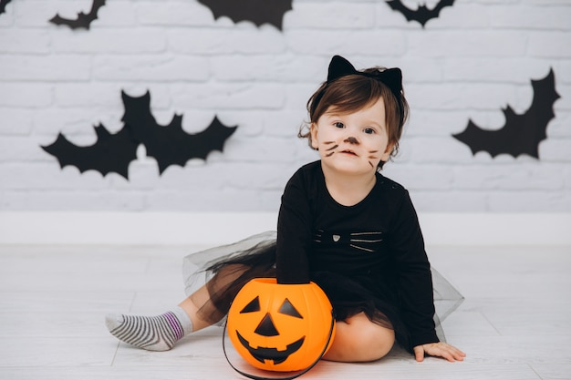 Une petite fille en costume de chat noir avec un panier de citrouilles