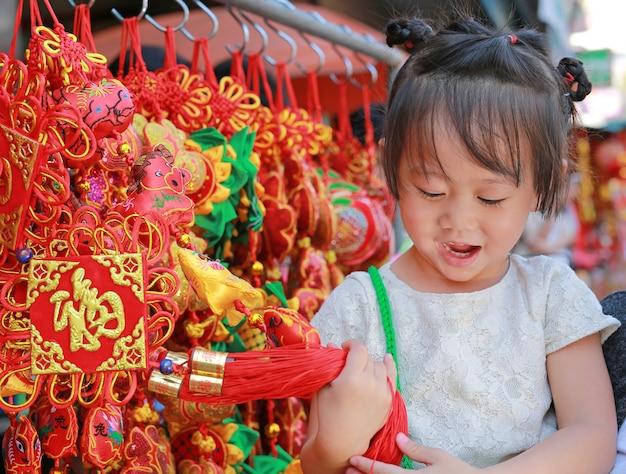La petite fille en costume chinois contre les décorations rouges chinoises est très populaire