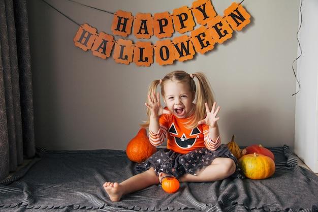 Une petite fille en costume de citrouille pour halloween, trick or treat. les enfants fêtent halloween. la fille est prête pour les vacances trick or treat