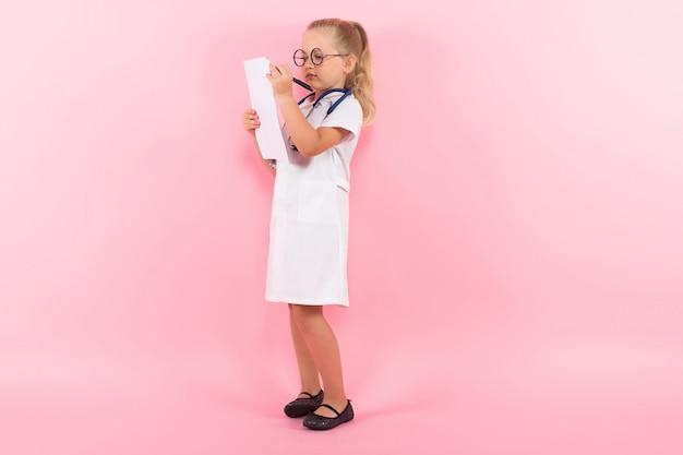Petite fille en costume de docteur avec du papier