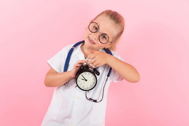 Petite fille en costume de docteur avec des horloges
