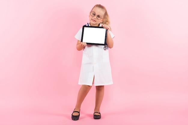 Petite fille en costume de docteur avec tablette
