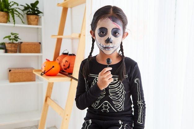 Petite fille en costume d'halloween à la maison
