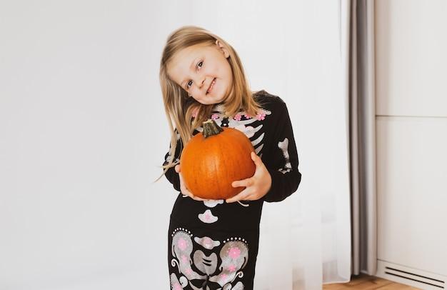Une petite fille en costume d'halloween sourit et tient une citrouille dans ses mains.