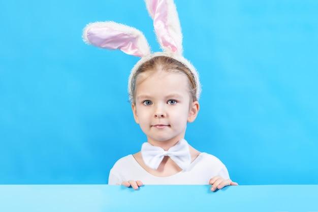 Petite fille en costume de lapin blanc bel enfant, symbole des vacances de pâques. copiez l'espace. disposition publicitaire.