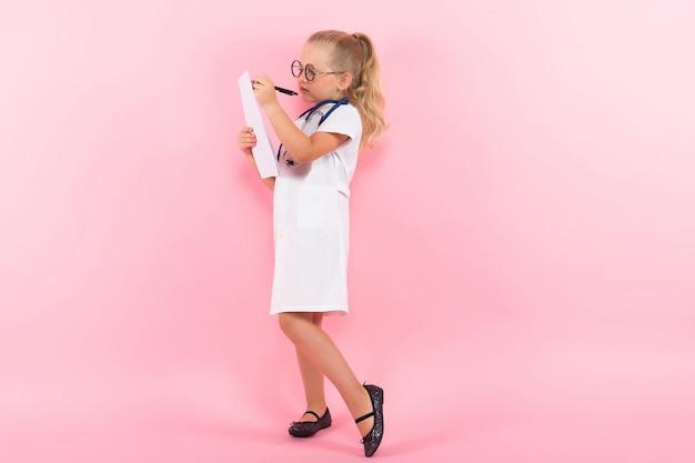 Petite fille en costume de médecin avec du papier