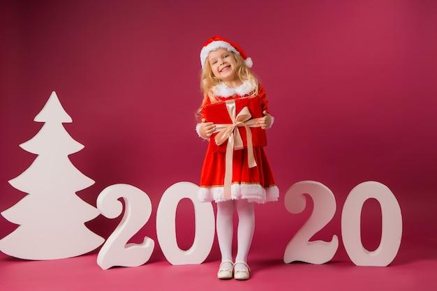 Petite fille en costume de père noël avec des numéros 2020