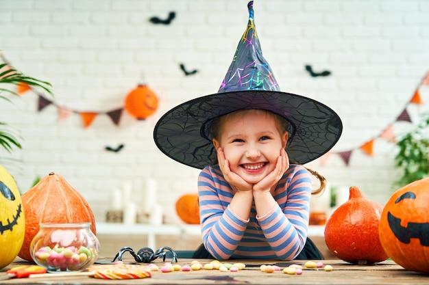 Une petite fille en costume de sorcière assis à une table