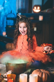 Petite fille en costume de sorcière avec baguette magique