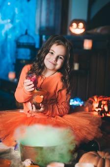 Petite fille en costume de sorcière faisant la potion