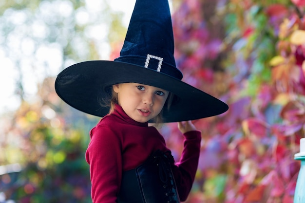 Petite fille en costume de sorcière faisant des visages différents sur la fête d'halloween dans le jardin
