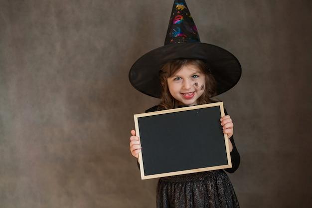 Petite fille en costume de sorcière halloween avec web et spyder sur son visage avec bureau noir