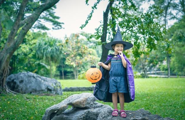 Petite fille en costume de sorcière tenant une lampe à l'halloween