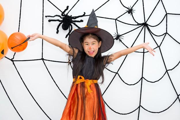 Petite fille en costume de sorcière tient la lanterne de jack
