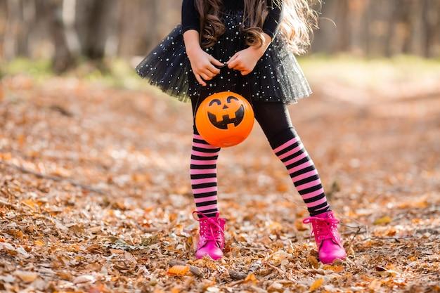 Une petite fille en costume de sorcière tient un seau de bonbons en forme de citrouille pour halloween