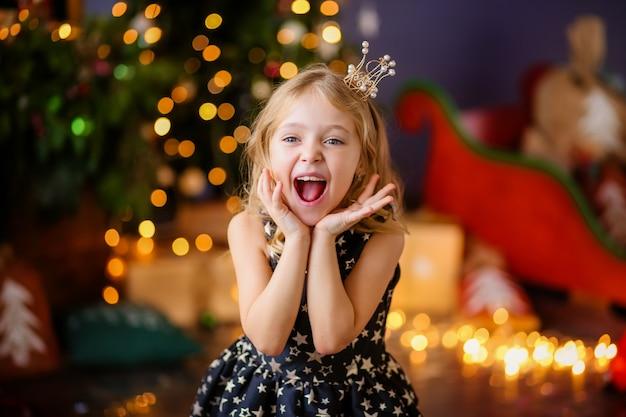 Petite fille à côté de l'arbre de noël