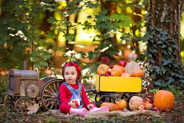 Petite fille à côté du tracteur avec un chariot avec des citrouilles