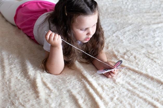 Une petite fille coud un jouet en feutre assis sur le lit sur une couverture beige; travaux d'aiguille