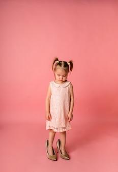Une petite fille coupable dans une robe de soirée rose se tient dans les chaussures de sa mère sur une surface rose avec un espace pour le texte