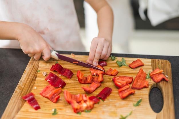 Petite fille coupe poivron rouge sur une planche à découper