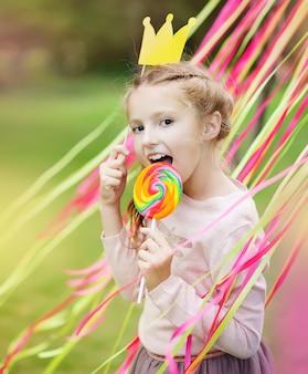 Petite fille avec une couronne en papier et une sucette lumineuse