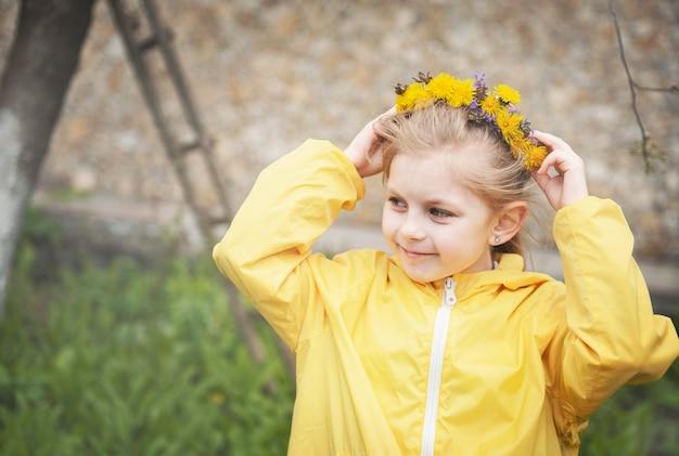Petite fille avec une couronne de pissenlits jaunes sur la tête