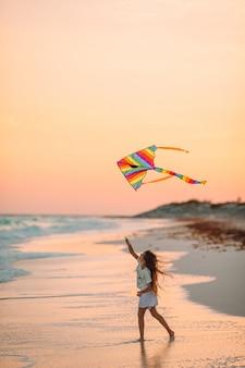 Petite fille en cours d'exécution avec cerf-volant sur une plage tropicale. enfant joue au bord de l'océan.