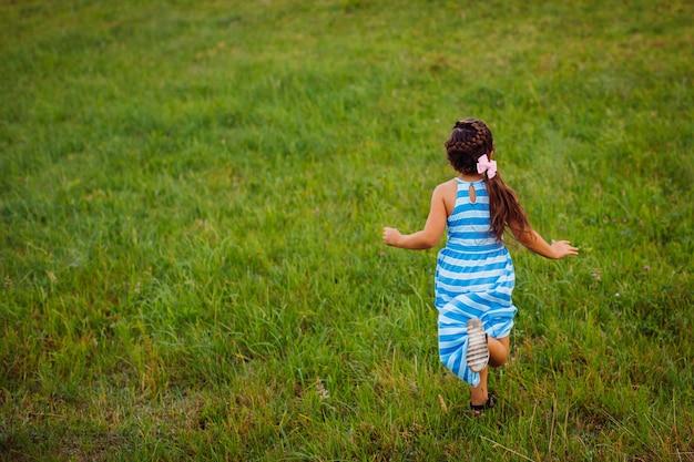Petite fille court sur le champ vert