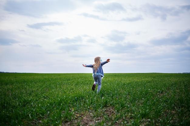 La petite fille court sur l'herbe verte sur le terrain, le printemps ensoleillé, le sourire et la joie de l'enfant, le ciel bleu avec des nuages