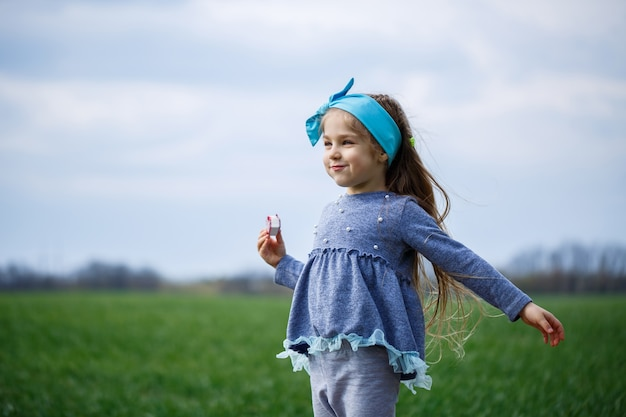 Une petite fille court et saute, de l'herbe verte sur le terrain, un temps printanier ensoleillé, le sourire et la joie de l'enfant, un ciel bleu avec des nuages