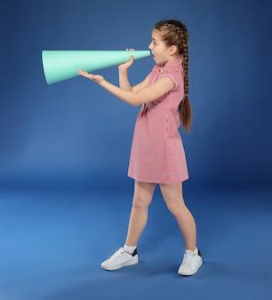 Petite fille criant dans un mégaphone en papier sur la couleur