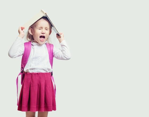 Petite fille criant tenant un cahier vierge au-dessus de sa tête sur fond blanc